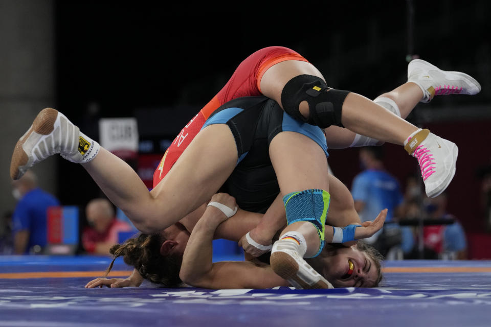 FILE - In this Aug. 2, 2021, file photo, Germany's Anna Carmen Schell, right, compete against Egypt's Enas Ahmed during their women's 68kg freestyle wrestling match at the 2020 Summer Olympics in Chiba, Japan. Tokyo Olympians are exercising extraordinary discipline against the coronavirus. They are sealed off in a sanitary bubble that has made competition possible but is also squeezing a lot of fun from their Olympic experience. (AP Photo/Aaron Favila, File)