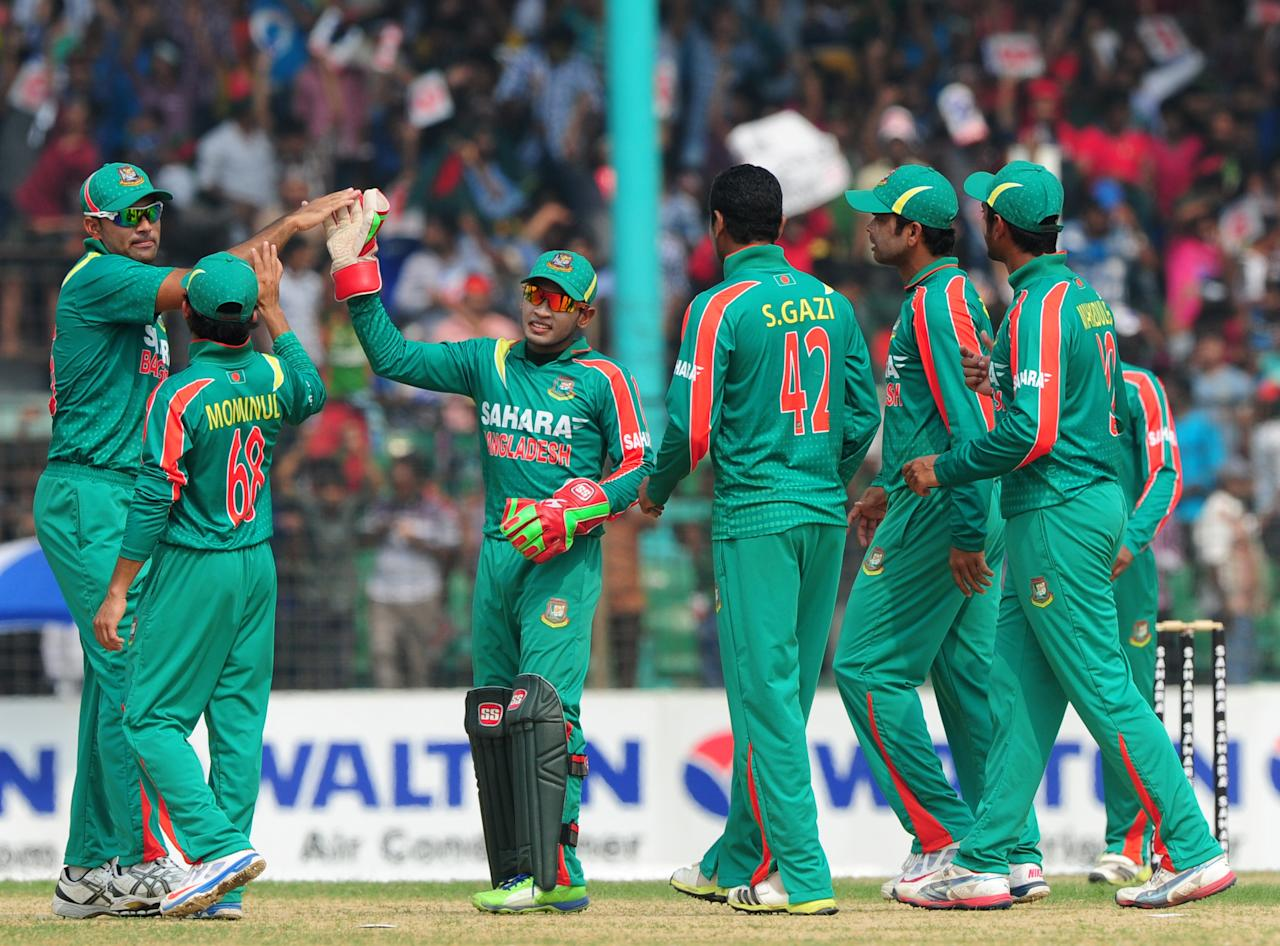 Bangladesh cricketers celebrate the wicket of New Zealand batsman Corey Anderson during the third One-Day International (ODI) cricket match between Bangladesh and New Zealand at Khan Jahan Ali Stadium in Fatullah, on the outskirts of Dhaka on November 3, 2013.   AFP PHOTO/ Munir uz ZAMAN        (Photo credit should read MUNIR UZ ZAMAN/AFP/Getty Images)