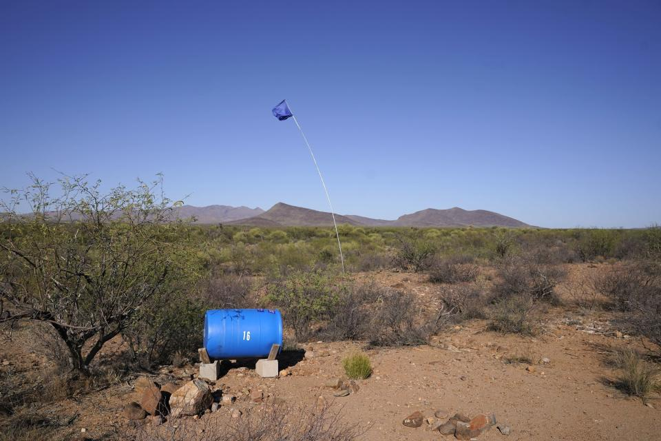 """A flag marks a water station set up for migrants by Humane Borders is checked by members of the Tucson Samaritans near Sasabe, Ariz., on Wednesday, May 19, 2021. """"I'm not looking forward to this summer,"""" said Douglas Ruopp, chairman of Humane Borders. """"No matter what we do, people keep dying."""" (AP Photo/Ross D. Franklin)"""