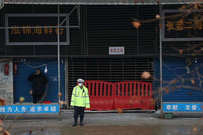A police officer wearing a mask stands in front of the closed seafood market in Wuhan, Hubei province, China January 10, 2020. The seafood market is linked to the outbreak of the pneumonia caused by the new strain of coronavirus. (Reuters)