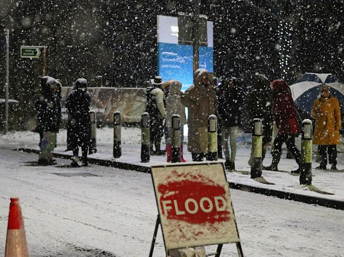 People cross a bridge over the River Mersey as snow falls in East Didsbury, Manchester, where homes are being evacuated due to risk of floodingPeter Byrne/PA