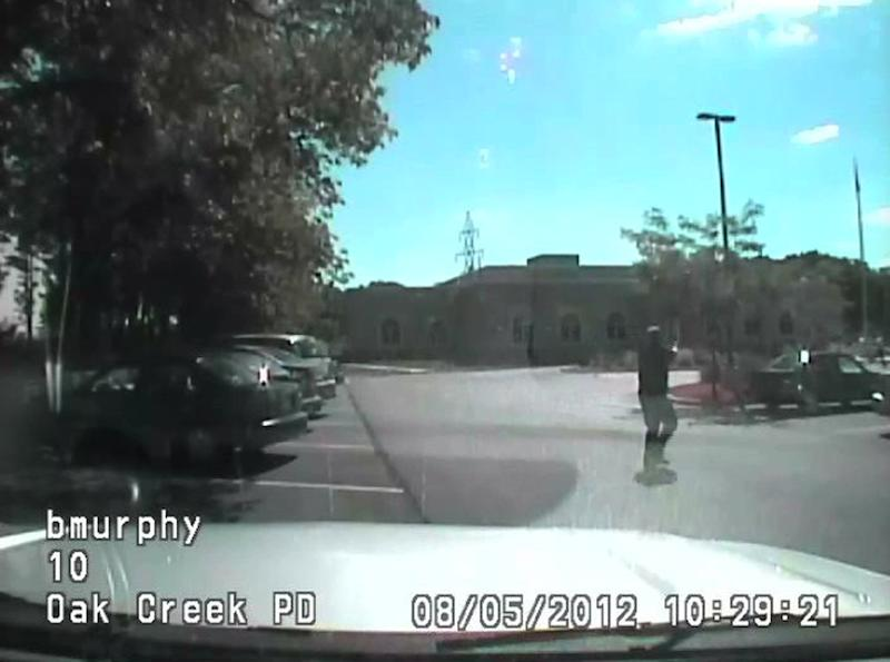 In this image taken from a Aug. 5, 2012 video from Oak Creek Police Lt. Brian Murphy's squad car camera, Lt. Murphy, the first officer on the scene, exchanges fire in the temple parking lot with shooter Wade Michael Page, rear right, as Page emerges from the temple. The video shows Murphy rolling behind a parked car for cover and Page chasing him down, firing multiple shots at him. Milwaukee County District Attorney John Chisholm says Murphy was hit 15 times. Page killed himself following a firefight with Officer Sam Lenda. (AP Photo/Oak Creek Police Department)