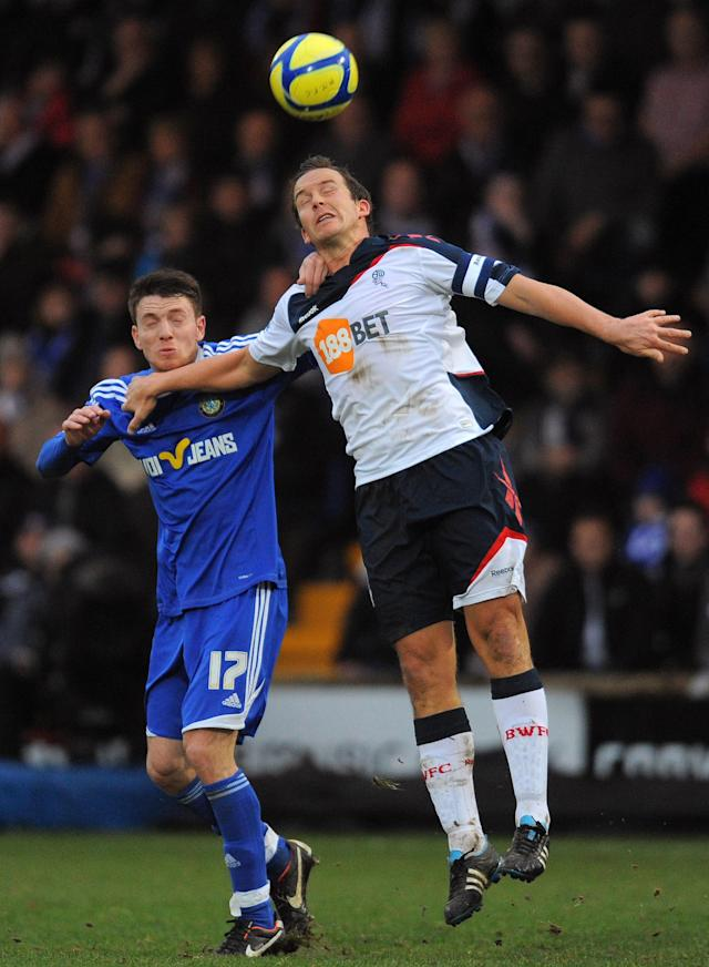 "Macclesfield Town's English midfielder Sam Wedgbury (L) vies with Bolton Wanderers' English forward Kevin Davies during the FA Cup football match between Macclesfield Town and Bolton Wanderers at Moss Rose,Macclesfield, north-west England, on January 7, 2012. AFP PHOTO/ ANDREW YATES. RESTRICTED TO EDITORIAL USE. No use with unauthorized audio, video, data, fixture lists, club/league logos or ""live"" services. Online in-match use limited to 45 images, no video emulation. No use in betting, games or single club/league/player publications. (Photo credit should read ANDREW YATES/AFP/Getty Images)"