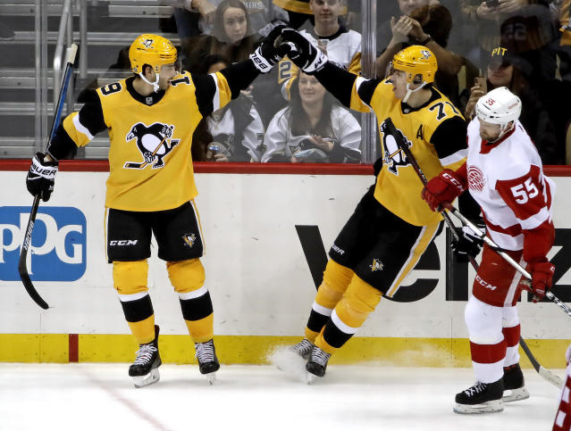 Pittsburgh Penguins' Derick Brassard (19) celebrates his empty-net goal with Evgeni Malkin (71) as Detroit Red Wings' Niklas Kronwall (55) skates back to the bench during the third period of an NHL hockey game in Pittsburgh, Thursday, Dec. 27, 2018. The Penguins won 5-2. (AP Photo/Gene J. Puskar)
