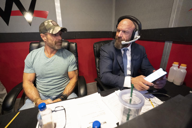 Shawn Michaels and Paul 'Triple H' Levesque sit side by side behind the scenes at an NXT event. (Photo courtesy of WWE)