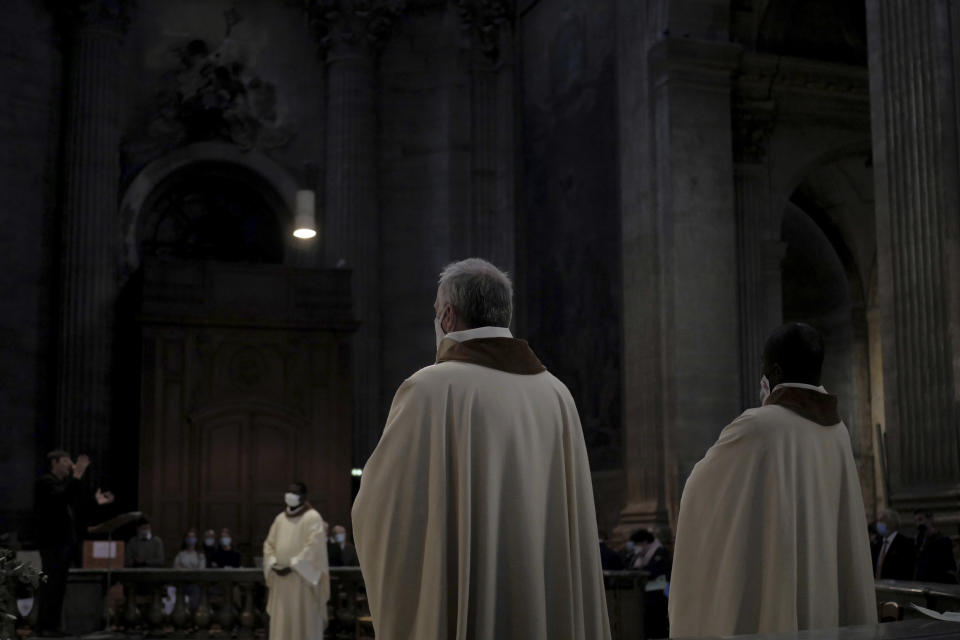 Priest assistants celebrate the All Saints Day mass in Saint-Sulpice church, in Paris, Sunday, Nov. 1, 2020. France heightened its security alert amid religious and geopolitical tensions around cartoons mocking the Muslim prophet. (AP Photo/Thibault Camus)