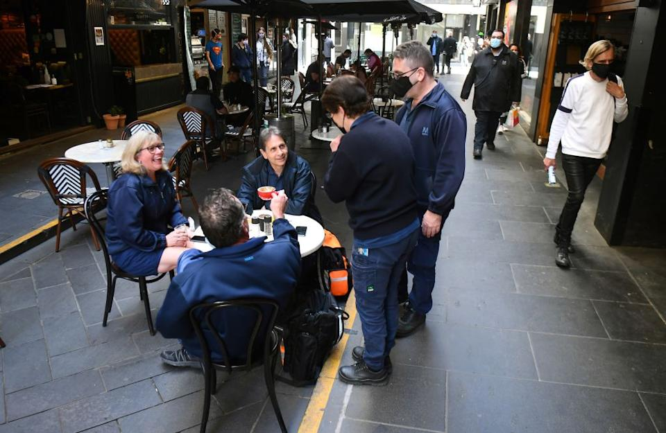 People enjoy a coffee together after measures to curb the spread of the Covid-19 coronavirus were eased allowing limited numbers of people back into shops, bars, cafes and restaurants in Melbourne.