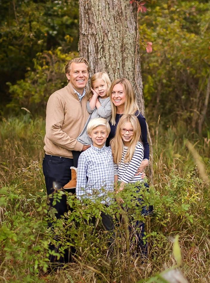 Abby Adair Reinhard, her husband Josh, and their three kids pose for a family photo in summer 2020.