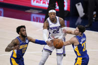 Sacramento Kings' Richaun Holmes (22) passes the ball between Indiana Pacers' Oshae Brissett (12) and Doug McDermott (20) during the first half of an NBA basketball game Wednesday, May 5, 2021, in Indianapolis. (AP Photo/Darron Cummings)