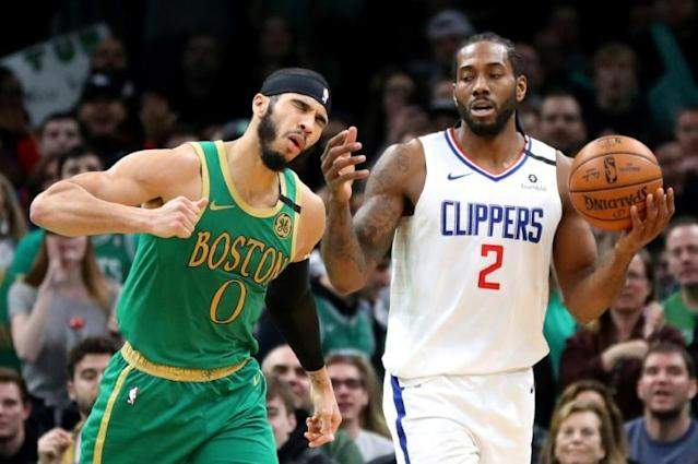 Boston's Jayson Tatum, left, reacts to a turnover by Kawhi Leonard of the Los Angeles Clippers on Thursday in Boston's 141-133 double-overtime triumph (AFP Photo/Maddie Meyer)