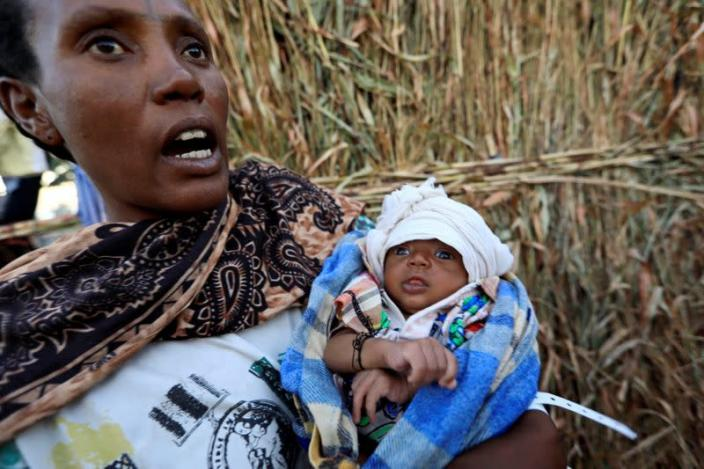 FILE PHOTO: An Ethiopian refugees fleeing from the ongoing fighting in Tigray region, holds her new born baby at the Um-Rakoba camp, on the Sudan-Ethiopia border, in the Al-Qadarif state