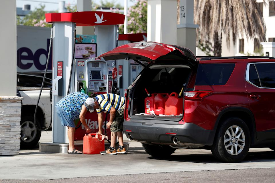 A couple fills up multiple 5 gallon gas tanks at a Wawa gas station, after a cyberattack crippled the biggest fuel pipeline in the country, run by Colonial Pipeline, in Tampa, Florida on May 12, 2021. (Octavio Jones/Reuters)