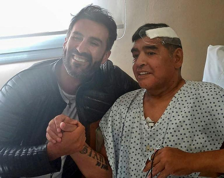 "Argentine football legend Diego Maradona (R) and his doctor Leopoldo Luque are pictured in Olivos, Argentina on November 11, 2020 Maradona is expected to leave hospital on Wednesday, eight days after undergoing surgery to remove a blood clot on his brain. Maradona ""has a signed discharge,"" and could go home, Leopoldo Luque told reporters outside a clinic in Buenos Aires"