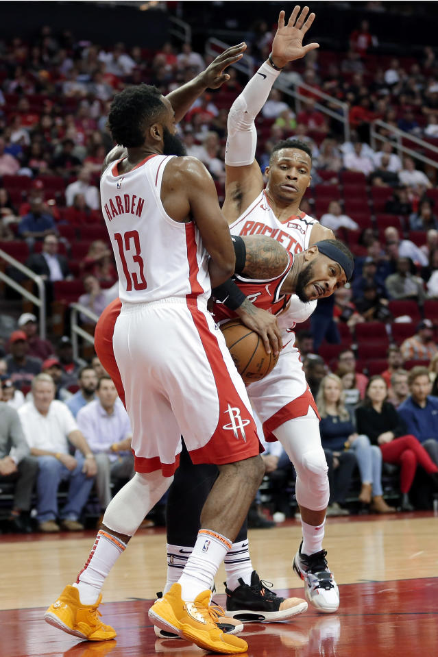 Portland Trail Blazers forward Carmelo Anthony, middle, is boxed up by Houston Rockets guard James Harden (13) and guard Russell Westbrook, back, during the first half of an NBA basketball game Wednesday, Jan. 15, 2020, in Houston. (AP Photo/Michael Wyke)