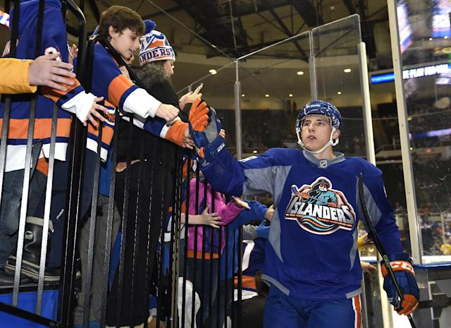 "Wearing the Fisherman jersey of the late 1990's, New York Islanders center Ryan Strome (18) high fives with fans as he comes off the ice after warmups before the NHL hockey game against the Florida Panthers at Nassau Coliseum on Tuesday, Feb. 3, 2015, in Uniondale, N.Y. The Islanders are celebrating their 43 years of history at the Nassau Coliseum and the team wore the special jerseys featuring the ""Fisherman"" crest during warmups. (AP Photo/Kathy Kmonicek)"