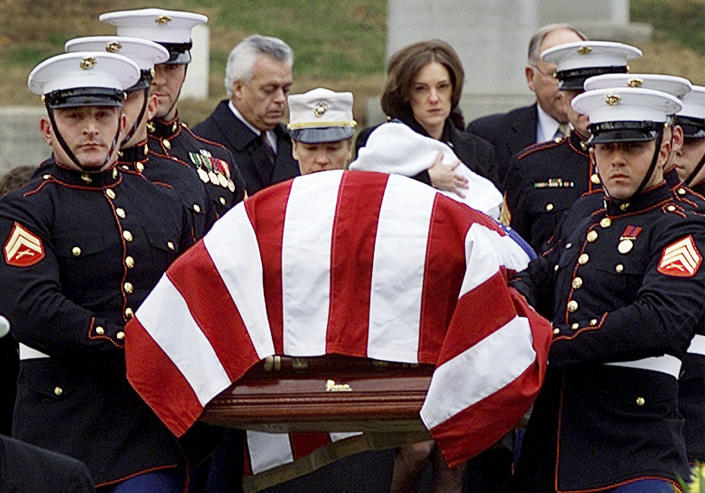 """FILE - In this Dec. 10, 2001, file photo Shannon Spann, wife of CIA officer Johnny Michael """"Mike"""" Spann, follows her husband's casket to the grave site, holding her 6-month old son Jake, at Arlington National Cemetery in Arlington, Va. Spann, a Marine turned CIA officer, felt a duty to go to Afghanistan in the wake of the Sept. 11, 2001, attacks. In November of 2001, the 32-year-old CIA paramilitary officer from Winfield, Ala., became the first of 2,448 American service members to be killed in Afghanistan. (AP Photo/Doug Mills, File)"""