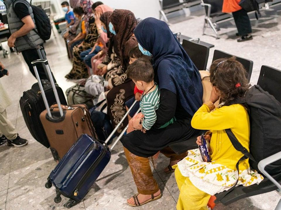 Refugees from Afghanistan wait to be processed after arriving on a evacuation flight at Heathrow Airport (PA)
