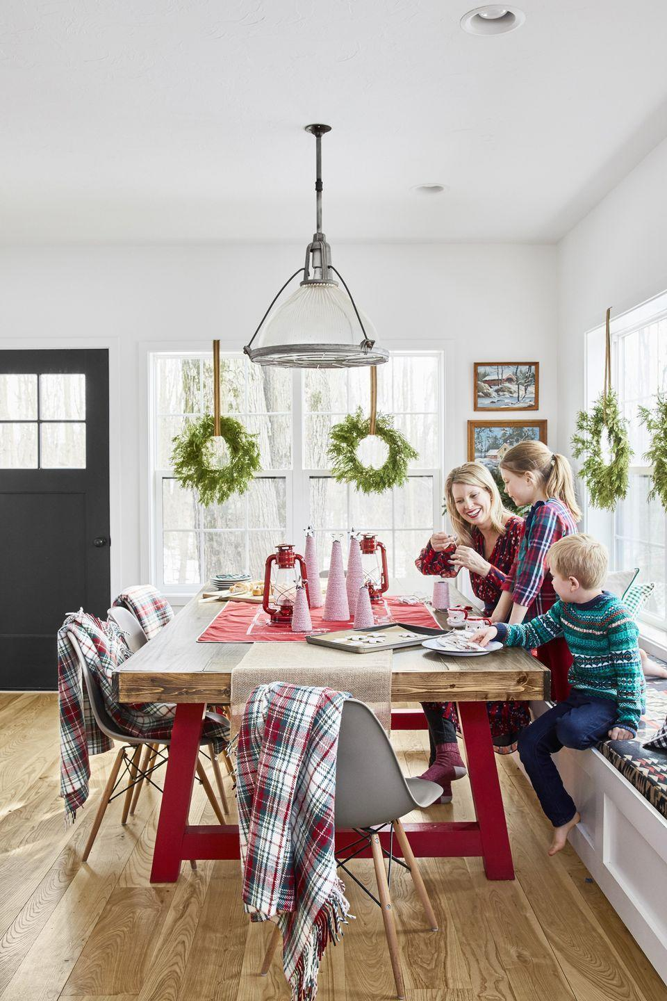 """<p>Crafting sessions take place around a dining room table complete with """"trees"""" made from <a href=""""https://www.amazon.com/FloraCraft-Styrofoam-Cone-Inch-White/dp/B0018NBAIE?tag=syn-yahoo-20&ascsubtag=%5Bartid%7C10050.g.1247%5Bsrc%7Cyahoo-us"""" rel=""""nofollow noopener"""" target=""""_blank"""" data-ylk=""""slk:Styrofoam cones"""" class=""""link rapid-noclick-resp"""">Styrofoam cones</a> covered in <a href=""""https://www.amazon.com/eBoot-Cotton-Kitchen-Cooking-Wrapping/dp/B019F7XP5A?tag=syn-yahoo-20&ascsubtag=%5Bartid%7C10050.g.1247%5Bsrc%7Cyahoo-us"""" rel=""""nofollow noopener"""" target=""""_blank"""" data-ylk=""""slk:baker's twine"""" class=""""link rapid-noclick-resp"""">baker's twine</a> and topped with <a href=""""https://www.amazon.com/Ann-Clark-Star-Cookie-Cutter/dp/B01GVUYT4U?tag=syn-yahoo-20&ascsubtag=%5Bartid%7C10050.g.1247%5Bsrc%7Cyahoo-us"""" rel=""""nofollow noopener"""" target=""""_blank"""" data-ylk=""""slk:star cookie cutters"""" class=""""link rapid-noclick-resp"""">star cookie cutters</a>.</p><p><a class=""""link rapid-noclick-resp"""" href=""""https://www.amazon.com/Ann-Clark-Star-Cookie-Cutter/dp/B01GVUYT4U?tag=syn-yahoo-20&ascsubtag=%5Bartid%7C10050.g.1247%5Bsrc%7Cyahoo-us"""" rel=""""nofollow noopener"""" target=""""_blank"""" data-ylk=""""slk:SHOP COOKIE CUTTERS"""">SHOP COOKIE CUTTERS</a></p>"""