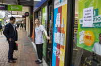 A staff member stands outside a pharmacy that closed for two hours in central Wellington, New Zealand, Wednesday, June, 23, 2021. After enjoying nearly four months without any community transmission of the coronavirus, New Zealanders were on edge Wednesday after health authorities said an infectious traveler from Australia had visited over the weekend. (Mark Mitchell/NZ Herald via AP)
