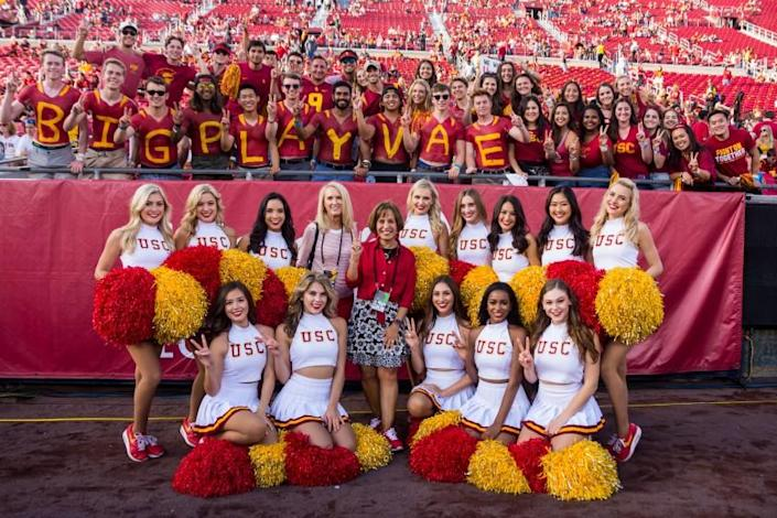 USC president Carol Folt (in red), center, poses with Lori Nelson (pink blouse) and the USC Song Girls.