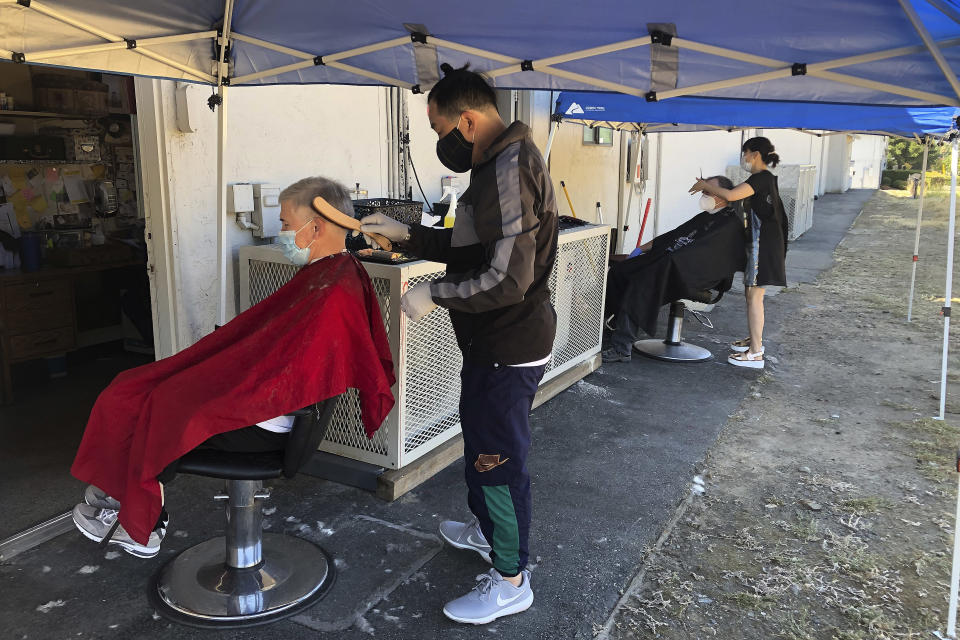 Customers of Cosmo's barber shop receive haircuts outdoors on Wednesday, July 22, 2020, in Pleasanton, Calif. Throughout May and June, California reopened much of its economy, and people resumed shopping in stores and dining in restaurants. But infections began to surge and a new round of business restrictions were imposed, including a ban on indoor dining in restaurants and bars. (AP Photo/Ben Margot)