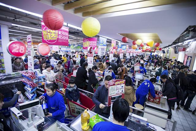 Chinese Customers wait in line to check out by Alipay to enjoy 50% off up to 50 yuan ($7.74) at a supermarket on December 12, 2015. REUTERS/Stringer