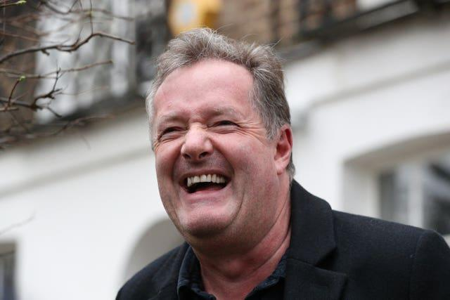 Piers Morgan laughs as he speaks to reporters outside his home in Kensington, central London