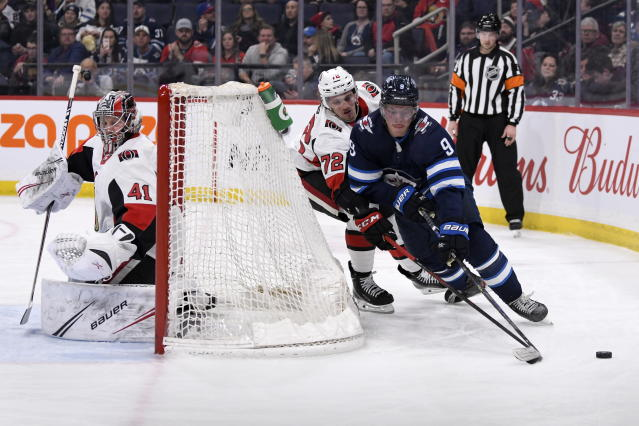 Winnipeg Jets' Andrew Copp (9) carries the puck behind Ottawa Senators' goaltender Craig Anderson (41) and Thomas Chabot (72) during second period NHL action in Winnipeg on Saturday, Feb. 8, 2020. (Fred Greenslade/The Canadian Press via AP)