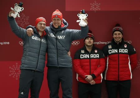 Bobsleigh - Pyeongchang 2018 Winter Olympics - Men's 2-man Finals - Olympic Sliding Centre - Pyeongchang, South Korea - February 19, 2018 - Gold medalists Francesco Friedrich and Thorsten Margis of Germany celebrate with gold medalists Alexander Kopacz and Justin Kripps of Canada during the victory ceremony. REUTERS/Edgar Su