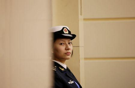 A female soldier of the PLA Navy stand stands guard at a news conference in Qingdao