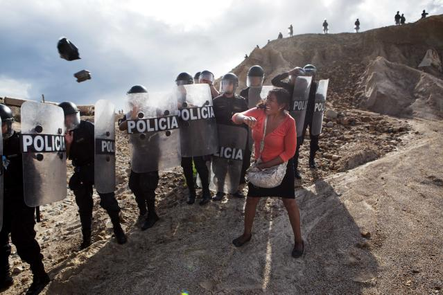 <p>A woman throws a rock and a bag at riot policemen who block her way home in Huepetuhe district in Peru's Madre de Dios region in Peru, Monday, April 28, 2014. (Photo: Rodrigo Abd/AP) </p>