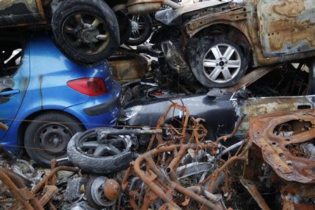 A blue Peugeot car is seen amongst other vehicles and motorcycles at an auto junkyard in Vendenheim near Strasbourg