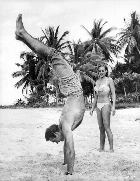 <p>Sean Connery doing a hand stand in the sand while Ursula Andress watches in amazement in a scene from the film 'Dr. No', 1962. </p>