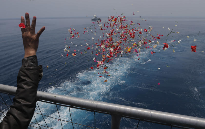 A relative sprinkles flowers during a prayer for the victims of the crashed Lion Air flight 610 on an Indonesia Navy ship in the waters where the airplane is believed to have crashed in Tanjung Karawang, Indonesia, Tuesday, Nov. 6, 2018. (AP Photo/Tatan Syuflana)