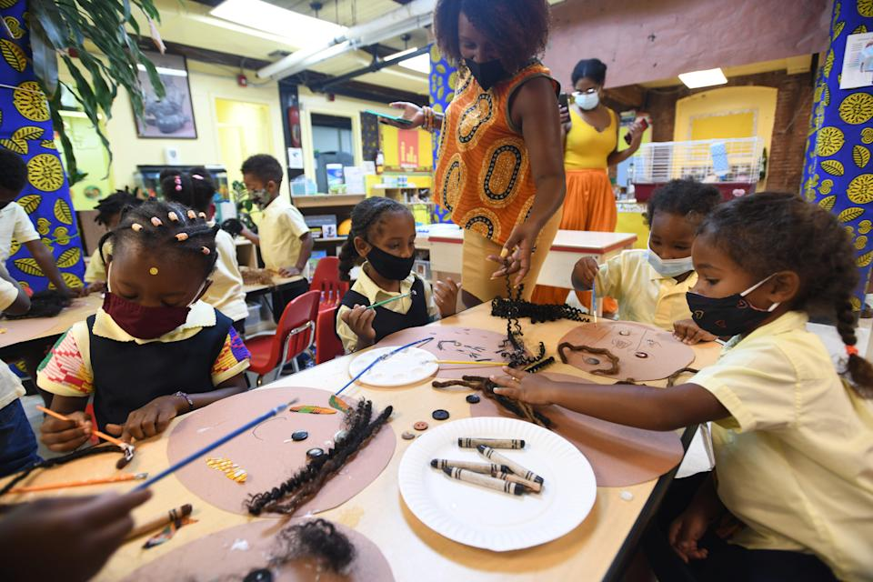 Aaliyah Barclift works with children as they create self-portraits at the Little Sun People preschool in Brooklyn, N.Y.