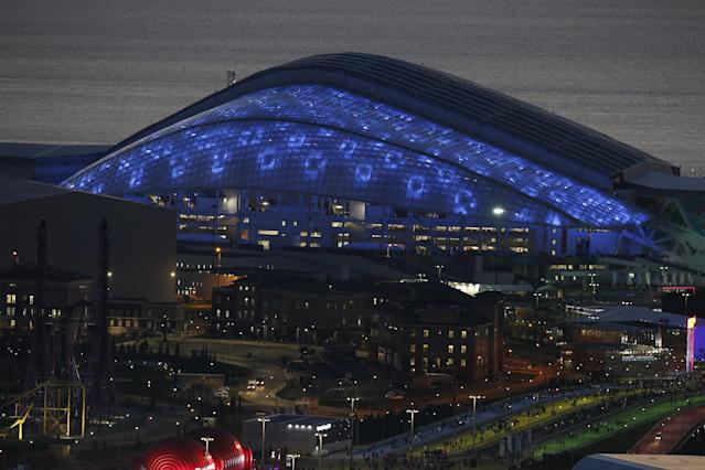 Fisht Olympic Stadium is illuminated Friday, Feb. 7, 2014, before the opening ceremony of the 2014 Winter Olympics, in Sochi, Russia. (AP Photo/Pavel Golovkin)