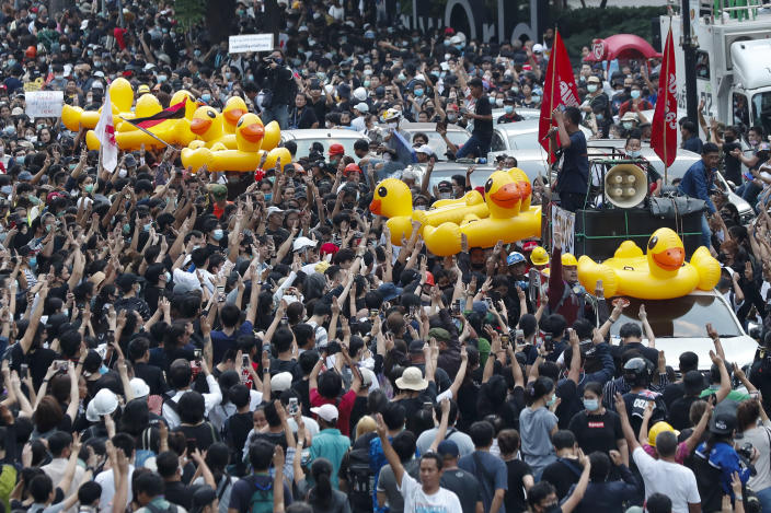 Large inflatable ducks are passed around the crowd at a pro-democracy rally in Bangkok, Thailand, Wednesday, Nov. 18, 2020. Police in Thailand's capital braced for possible trouble Wednesday, a day after a protest outside Parliament by pro-democracy demonstrators was marred by violence that left dozens of people injured. (AP Photo/Sakchai Lalit)