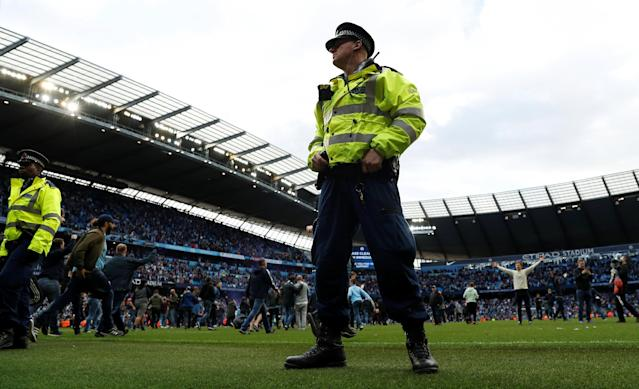 "Soccer Football - Premier League - Manchester City v Swansea City - Etihad Stadium, Manchester, Britain - April 22, 2018 Manchester City fans invade the pitch as police look on after the game Action Images via Reuters/Lee Smith EDITORIAL USE ONLY. No use with unauthorized audio, video, data, fixture lists, club/league logos or ""live"" services. Online in-match use limited to 75 images, no video emulation. No use in betting, games or single club/league/player publications. Please contact your account representative for further details."