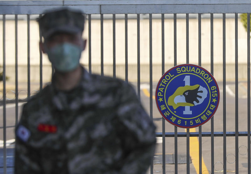 A South Korean marine wearing a mask stands in front of the Navy Base on Feb. 21, 2020, after a soldier of the unit was confirmed to have been infected with the coronavirus on Jeju Island, South Korea.(Woo Jang-ho/Yonhap via AP)