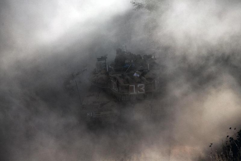 Israeli soliders are seen on a Merkava tank, as part of the Israeli army deployment near Israel's border with the Gaza Strip on July 20, 2014