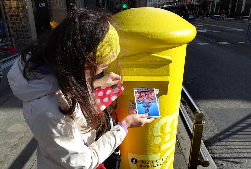 Madrid, Spain - December 13, 2016: Woman drops postcard in a street postbox of Correos, the national postal service of Spain.