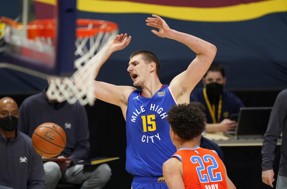 Denver Nuggets center Nikola Jokic, back, reacts after Oklahoma City Thunder center Isaiah Roby tried to steal the ball in the first half of an NBA basketball game Friday, Feb. 12, 2021, in Denver. (AP Photo/David Zalubowski)