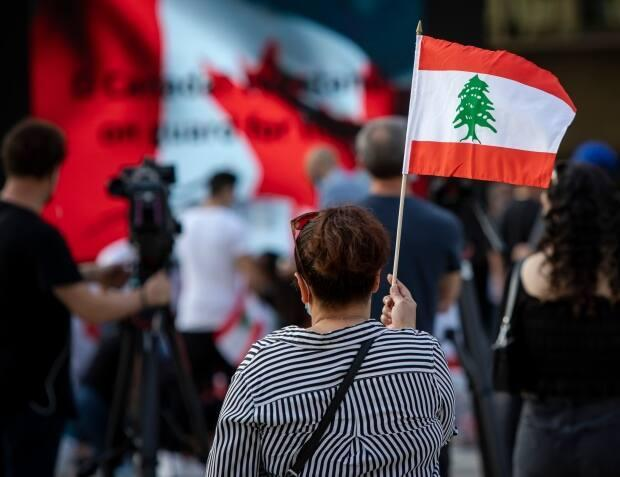 Hundreds lit candles, signed a board entitled 'letters for Beirut' and carried Lebanese flags in Nathan Phillips Square last summer as they remembered those who died in the explosion. They listened to speakers and held a moment of silence. (Evan Mitsui/CBC - image credit)