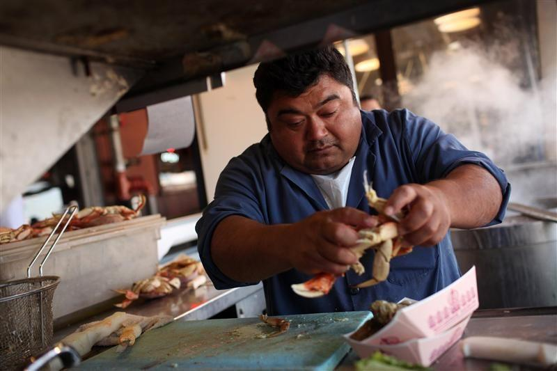 Marco Palomo prepares fresh steamed crab at Fisherman's Wharf in San Francisco, California.