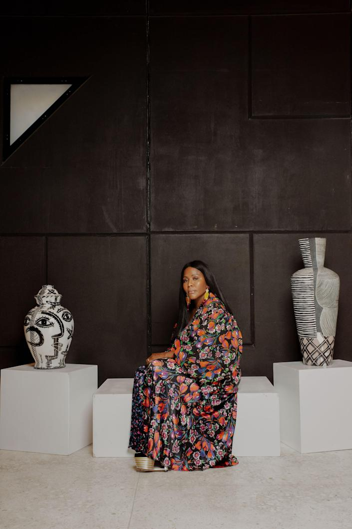 Reni Folawiyo, wearing a dress and Jacket by Duro Olowu, Mercedes Salazar earrings, and Salvatore Ferragamo shoes, in between an abstract portrait vessel by Charmaine Haines and a Louise Gelderblom vase.