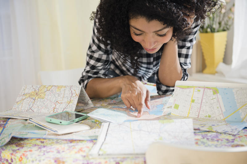 woman planning road trip with maps