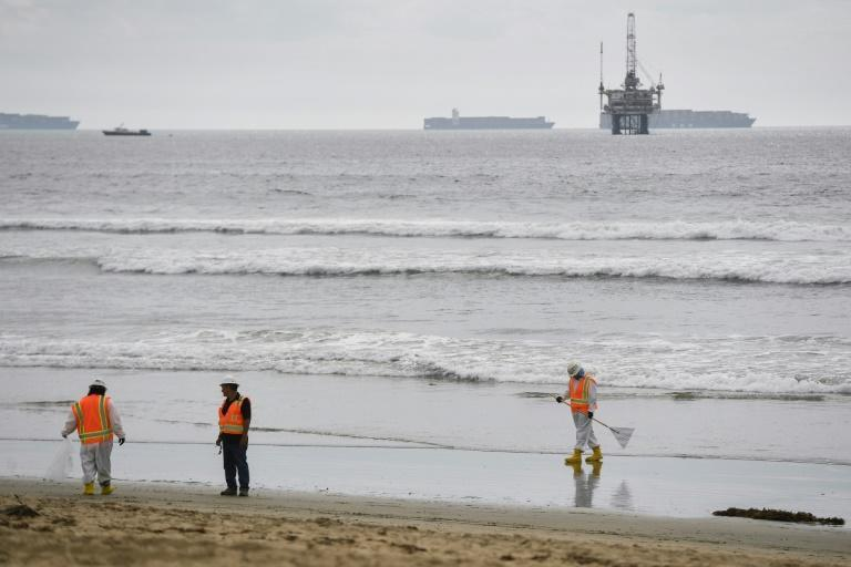 An oil platform and cargo container ships are seen on the horizon as environmental response crews clean the beach after an oil spill in the Pacific Ocean in Huntington Beach, California on October 4, 2021 (AFP/Patrick T. FALLON)