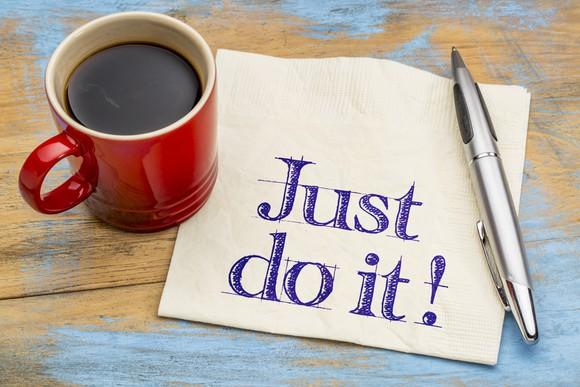 red mug of black coffee next to pen and napkin on which is written just do it!