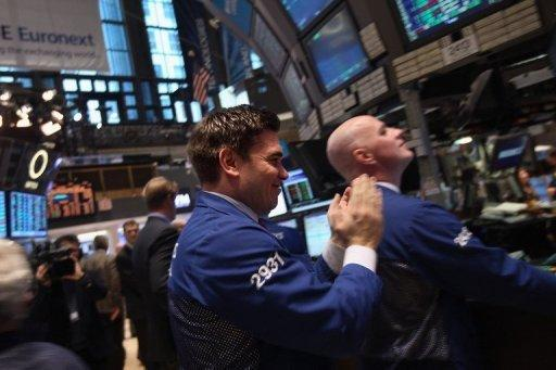 A trader applauds while working on the floor of the New York Stock Exchange on February 21