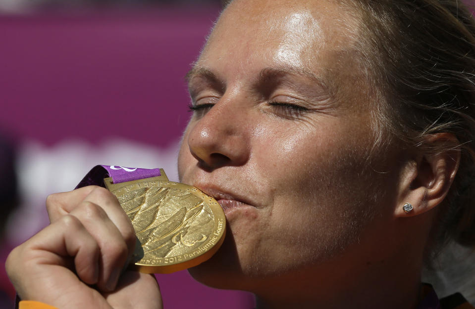 -FILE- In this Friday, Sept. 7, 2012, file image, Esther Vergeer of the Netherlands kisses her gold medal for winning the women's wheelchair tennis final at the 2012 Paralympics games, in London. Esther Vergeer, the retired Dutch wheelchair tennis star who went on a 470-match winning streak during her record-breaking career, has been diagnosed with breast cancer. (AP Photo/Alastair Grant, File)